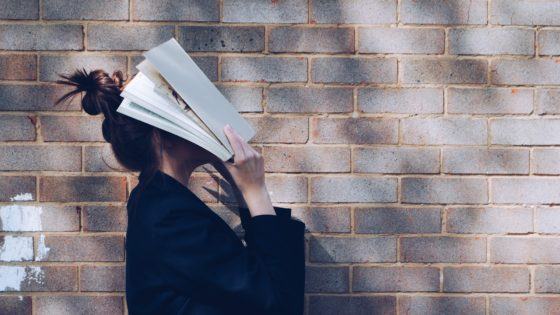 woman holds book to face